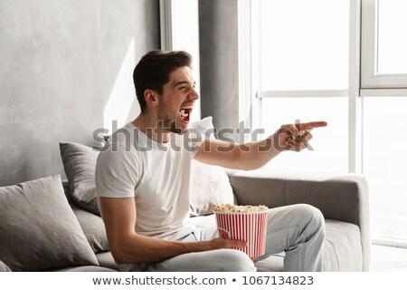 Elragadtatott boldog férfi ül kanapé nappali Stock fotó © deandrobot