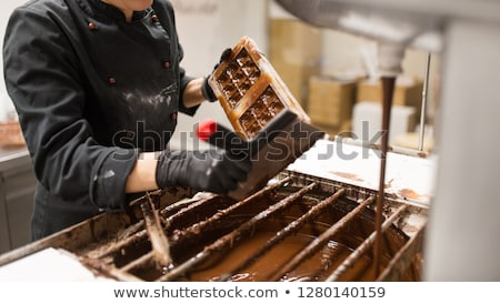 confectioner cleaning chocolate mold by spatula Stock photo © dolgachov