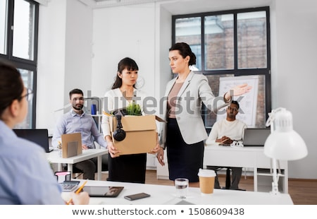sad female office worker packing personal stuff Stock photo © dolgachov