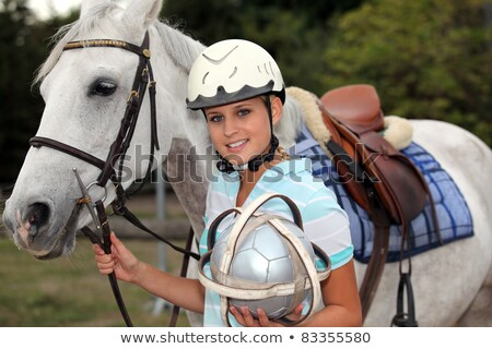 Stock photo: professional female jockey posing with her horse