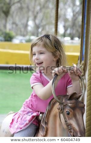 little blond girl playing horses merry go round stock photo © lunamarina