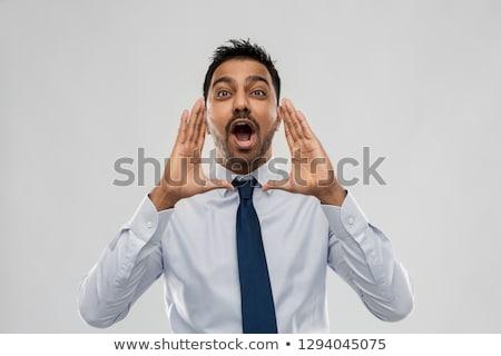indian businessman shouting or calling over grey Stock photo © dolgachov