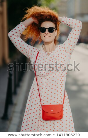 Stock fotó: Cheerful Beautiful Woman With Crisp Red Hair Keeps Hands On Head Wears Sunglasses And White Dress
