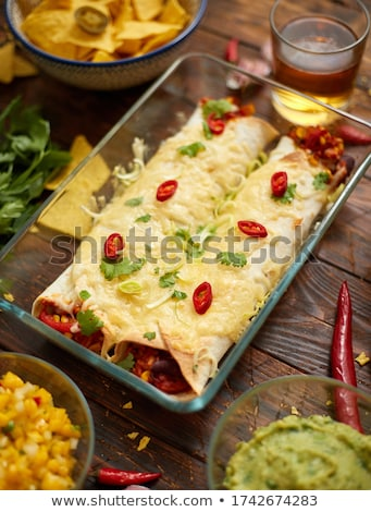 Vegetable Burritos served in glass heatproof dish. With salsa, guacamole, nachos and ingredients Stock photo © dash