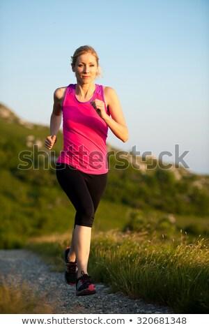Woman running. Trail runner in cross country run. Female runner training jogging outdoors in mountai Stock photo © Maridav