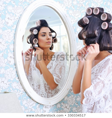 Beautiful woman putting rollers in her hair Stock photo © photography33