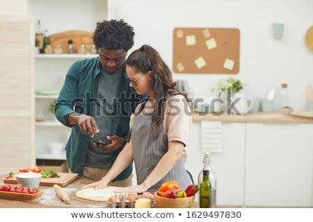 Fiatalember konyha készít pizza kötény étel Stock fotó © elly_l