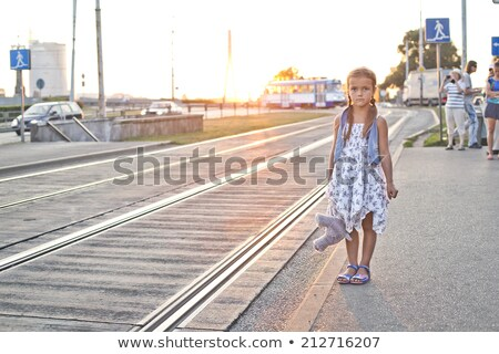 Lonely girl waiting on a city tram station stock photo © Kor