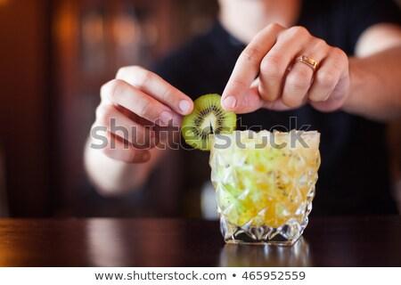 barman is decorating cocktail with slise kiwi at night club con stock photo © yatsenko