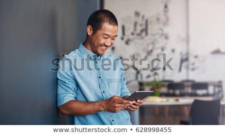 Işadamı bakıyor dijital tablet genç Stok fotoğraf © filipw