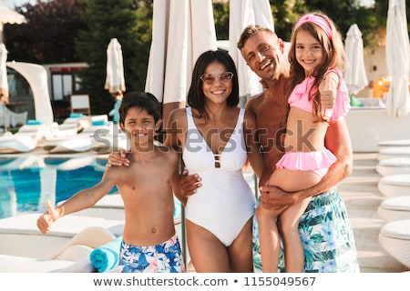 Photo of amazing caucasian family with children resting near lux Stock photo © deandrobot