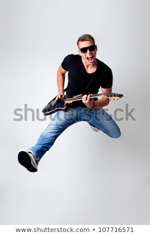 young rock star performing on guitar and smiling Stock photo © feedough
