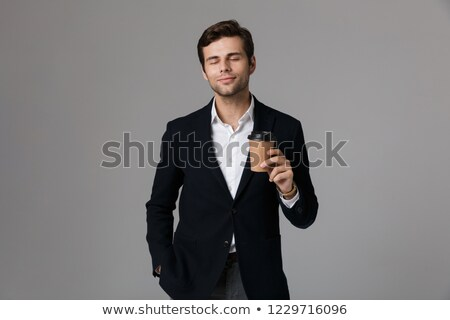 Image of unshaved man 30s in businesslike suit holding coffee an Stock photo © deandrobot