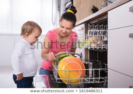 Girl Helping Her Mother To Unload Dishwasher Stock photo © AndreyPopov