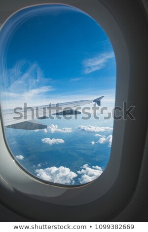 View of cloudy blue clear sky through airplane porthole. Stock photo © artjazz