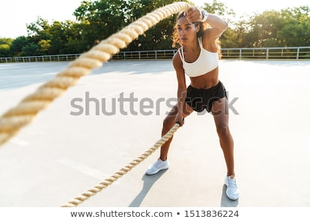 Image of nice african american sportswoman doing exercise Stock photo © deandrobot