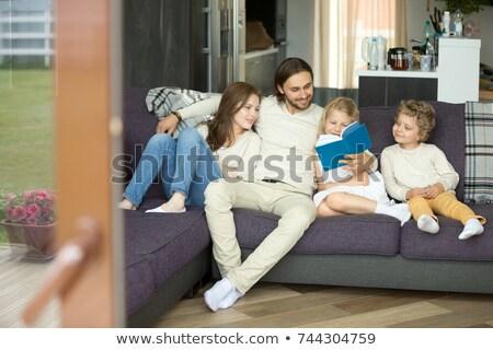 Happy family on the couch reading storybook Stock photo © wavebreak_media