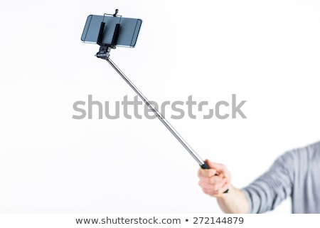 Stock photo: Casual man using a selfie stick