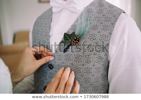 bride adjusting boutonniere on grooms jacket stock photo © dashapetrenko