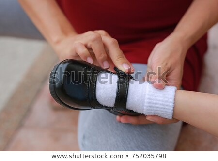 Mother helping child put on shoes Stock photo © bluering
