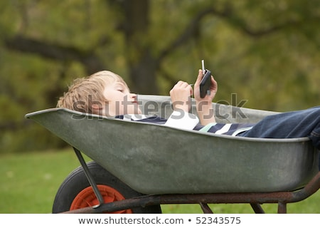 young boy laying wheelbarrow using smart mobile phone stock photo © monkey_business