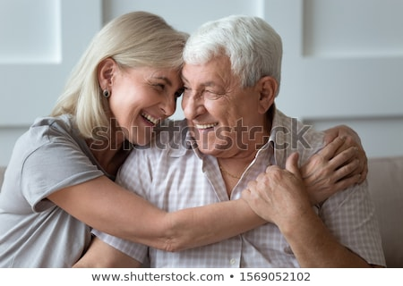 Caring husband embraces wife with love, have glad expressions, holds paper documents, discuss bankin Stock photo © vkstudio
