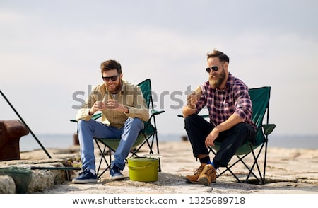 happy friends fishing and eating sandwiches Stock photo © dolgachov