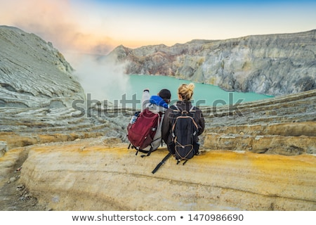 Young tourist man and woman sit at the edge of the crater of the Ijen volcano or Kawah Ijen on the I Stock photo © galitskaya
