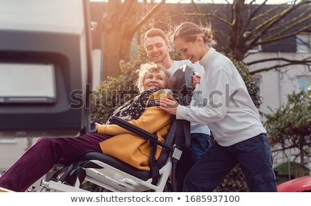 Two helpers picking up disabled senior woman for transport Stock photo © Kzenon