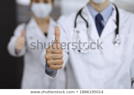 Doctor with thumbs up hand sign during viru diseases pandemic Stock photo © lovleah