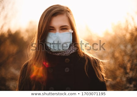 Portrait of the young girl in medical mask outdoors in sunset Stock photo © dashapetrenko