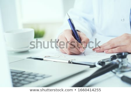 Closeup on a doctor writing on notepad stock photo © photography33