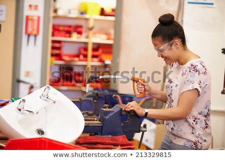 Female plumber sawing pipe Stock photo © photography33