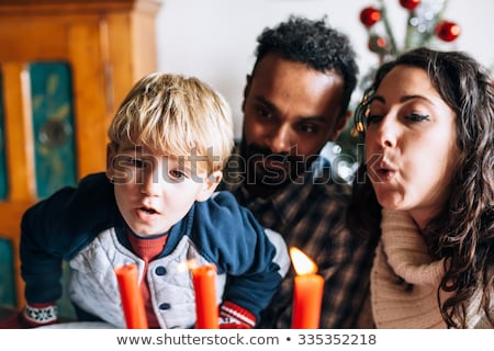 Stock photo: Child extinguishing Christmas candles
