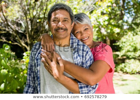 couple embracing each other in garden on a sunny day stock photo © wavebreak_media