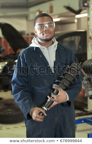student carrying car part in garage stock photo © is2