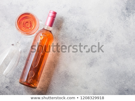 Bottle and glasses of pink rose wine on stone kitchen table background. Top view. Space for text Stock photo © DenisMArt