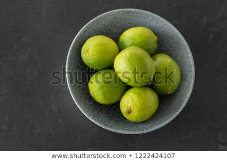 close up of whole limes in bowl on slate table top Stock photo © dolgachov