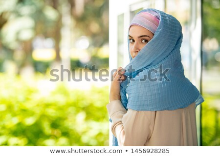 Young attractive Arabian woman in hijab looking at you over her shoulder Stock photo © pressmaster