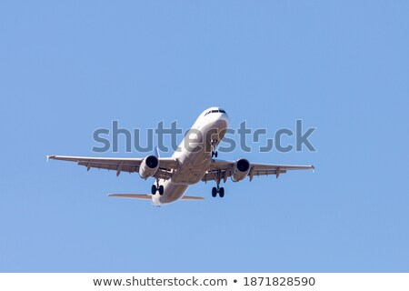 Stock photo: A white airplane flying in a clear pale blue sky