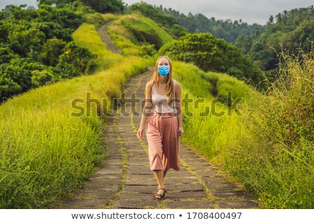 Young woman traveler in medical mask in Campuhan Ridge Walk , Scenic Green Valley in Ubud Bali Touri Stock photo © galitskaya