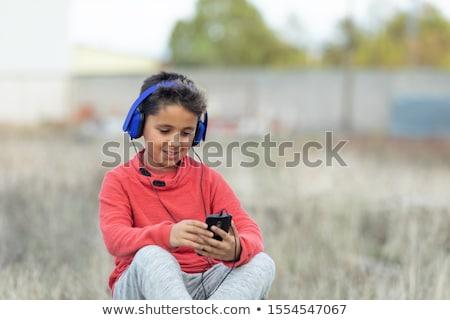 Criança cabelo escuro escuta música azul móvel Foto stock © Gelpi