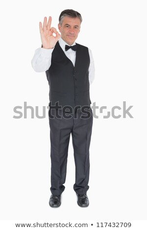 Smiling waiter in suit showing ok sign stock photo © wavebreak_media