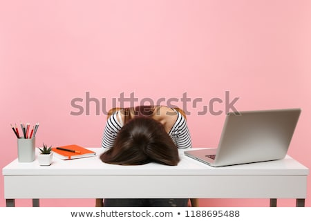 young tired business woman with headache sitting at computer in stock photo © dacasdo