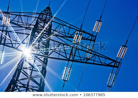 Electricity pylons against blue sky and sun rays Stock photo © posterize