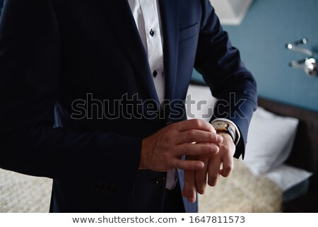 man in tuxedo puts on watch Stock photo © ssuaphoto