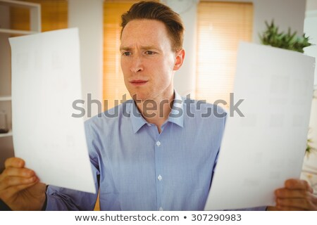 serious businessman holding two paper sheets stock photo © wavebreak_media