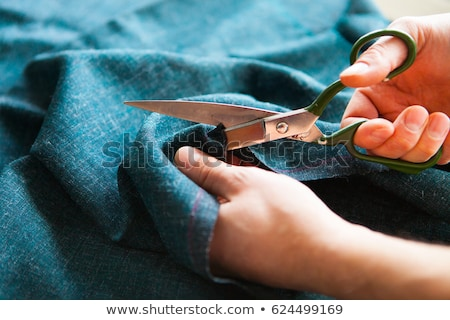 Detail of hands with scissors at tailor shop cutting cloth Stock photo © Kzenon