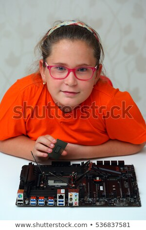Little girl installs CPU to motherboard Stock photo © Mikko