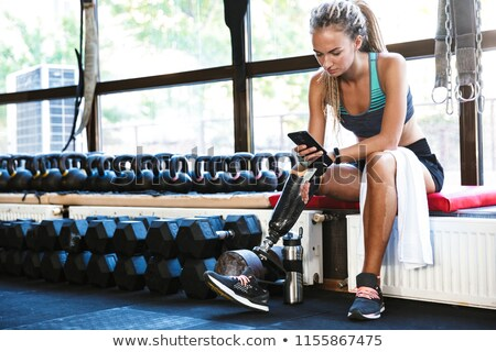 Disabled sports woman sitting in gym using mobile phone. Stock photo © deandrobot